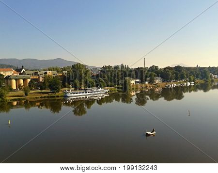 Litomerice Czech republic - august 19 2012: small dinghy with fisherman and big cruise ship on european river Elbe in Litomerice city in sommer when viewed from Tyrsuv most bridge