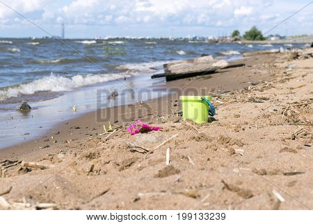 children's toy pail and a rake on the sand of the sea coast water sea