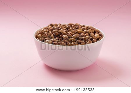 Raw pinto bean in a bowl on pink background. Vegan source of protein.
