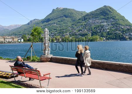 People Sitting And Walking On The Lakeside Of Lugano