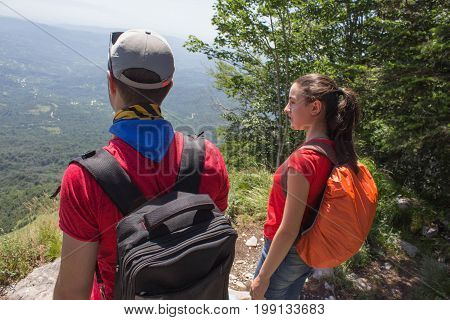 Eco tourism and healthy lifestyle concept. Young hiker girl end boy with backpack. Active hikers