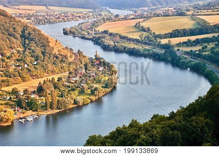 European river Elbe in Cirkvice village when viewed from Mlynaruv kamen lookout in czech central mountains tourist area at sommer sunset