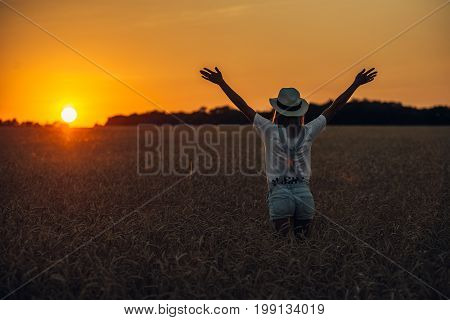 Young girl with outspread hands standing standing in the wheat field at sunset