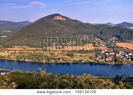 European river Elbe in Cirkvice village under Deblik hill when viewed from Mlynaruv kamen lookout in czech central mountains tourist area at sommer sunset