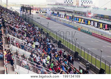 Delhi, India - 19th Mar 2017: Indian men, women, families sitting in the stands and watching a racing circuit