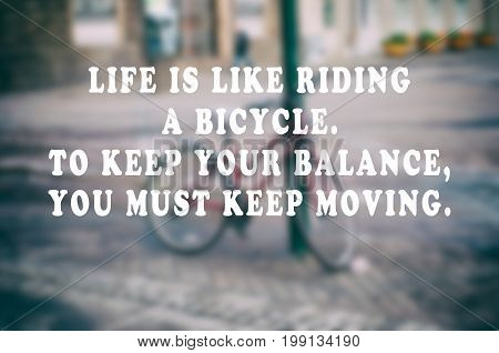 Inspirational and motivational quotes -Life is like riding a bicycle. To keep your balance you must keep moving. Retro styled blurry background.