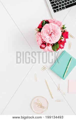 Flat lay home office desk. Female workspace with laptop pink and red roses bouquet golden accessories mint diary on white background. Top view feminine background.