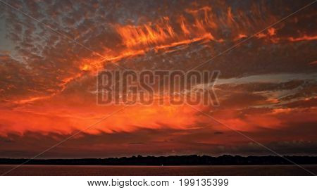 Orange Cloudy Sunset Seascape with sea water reflections. Photographed on the Australian East Coast.