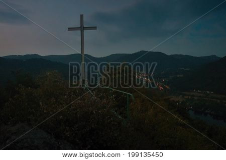 Big Christian cross on the way to Mlynaruv kamen lookout to valley of european river Labe in Czech central mountains tourist area in sommer night