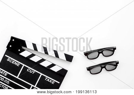 Filmmaker accessories. Clapperboard and glasses on white background top view.