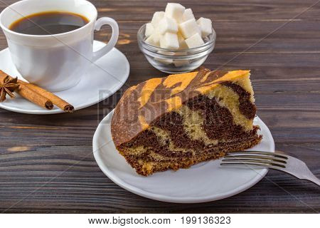 A cup of coffee with cinnamon sticks on a small plate a fork delicious piece of cake and a bowel with sugar cubes on dark wooden background