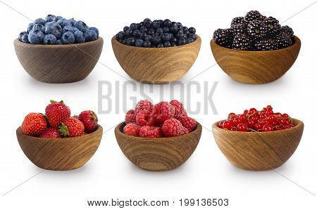 Black-blue and red berries isolated on white background. Collage of different fruits and berries. Blueberry bilberry blackberries strawberry red currant and raspberry. Collection of fruits and berries in a bowl.