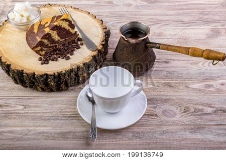 A delicious cake on wooden stump with a coffee cup fork tea spoon coffee beans and bowl with sugar cubes on a wooden background
