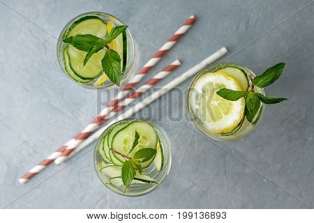 Refreshment Cocktails With Cucumber, Lemon And Mint On Gray Background.