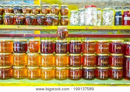 Homemade food products honey of several plants lavender rosemary pomegranate sage and mandarin and jam of several types of fruit figs mandarin and plum displayed at a food stand.
