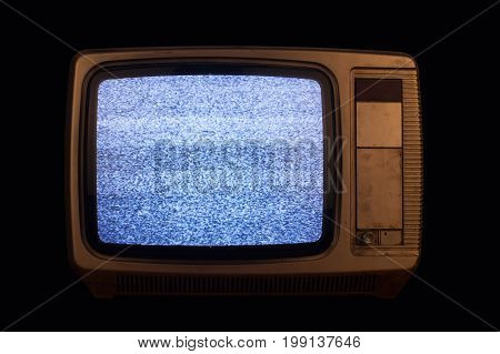 front view of old home TV set receiver with noise screen on black background