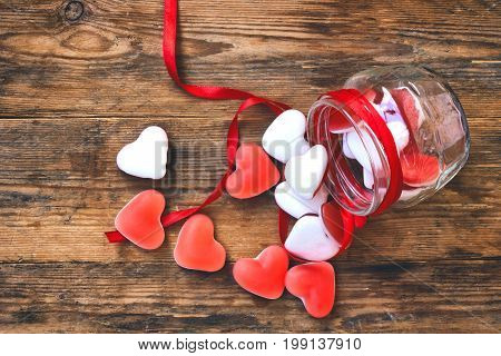 Marmalade candy shape heart in glass jar with ribbon on wooden table gift for Valentine's Day