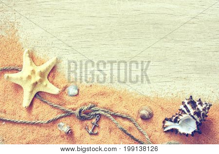 Marine theme background sand seashells rope with knot anchor on wooden table vacation concept vintage toned top view