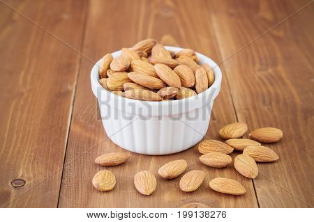 Almonds nuts in white bowl on wooden background. Source of healthy fat. Vegan source protein