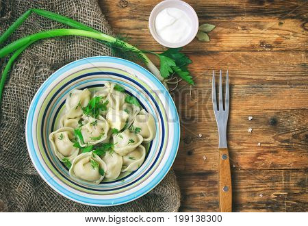 Dumplings with herbs sour cream napkin burlap on wooden table traditional russian cuisine