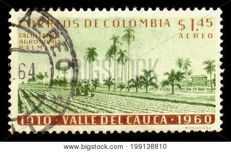 Colombia - circa 1961: A stamp printed in Colombia shows tractor on the field and agricultural college, Palmira in Colombia, circa 1961