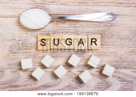 Diabetes block wooden letters with Refined sugar and sugar pile on a spoon