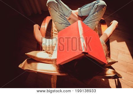 Hipster student napping in comfortable modern chair with paper book on head. Natural light. Bright sunny day. Knowledge and learning concept. Bookworm woman. Tired Girl. Top view. Preparing for exams