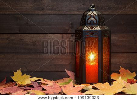 Glowing lantern with autumn leaves on a wood background