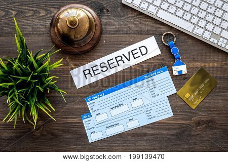 Preparing to trip. Book hotel and tickets. Airplane tickets near service bell and bank card on dark wooden table top view.