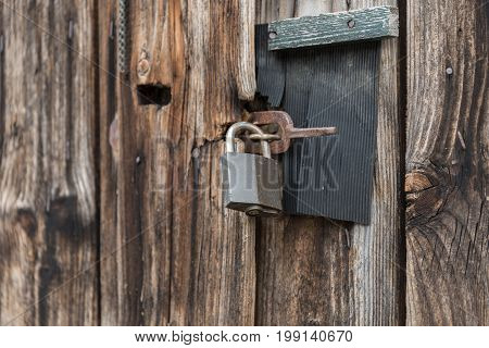 Old barn gate with a padlock locked - close-up