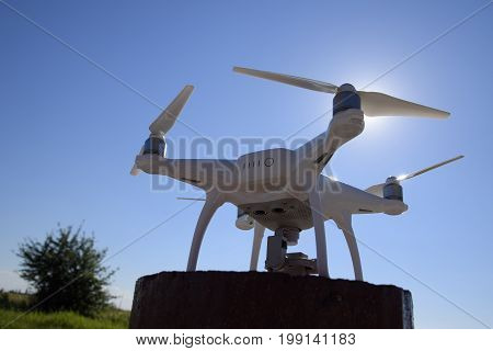 Quadrocopter Phantom 4 Against The Blue Sky In The Sun. Backlight. Dron Is An Innovative Flying Robo