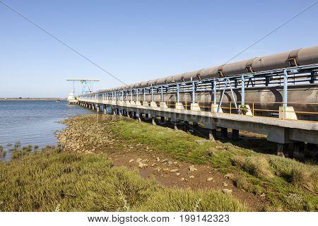 Oil pipeline at the riverbank of Rio Tinto river in Huelva Spain