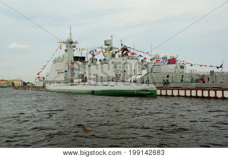 Military ships and submarine on the Neva river in St. Petersburg preparation for naval parade