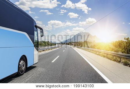 Tourist bus rushes along the asphalt high-speed highway.