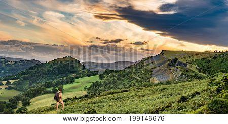 Senior male hiker looking at sunset panorama of Castell Dinas Bran near Llangollen from Panorama Walk