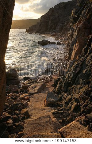 Rugged rocky shoreline with cliffs, waves, and stepping stones late evening in Baja, Mexico