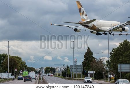 London UK - August 8 2017: Large jet Airbus A380 Etihad airlines landing at London Heathrow airport low above busy Great South-West road.