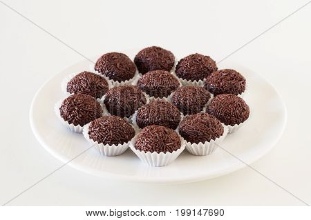 Brigadeiros. Traditional Brazilian chocolate truffles on white plate