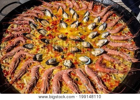 Seafood paella in a paella pan at a street food market.