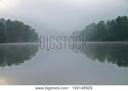 fog rises from Lake Chatuge early in the morning