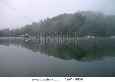 fog rises from the water at dawn over Lake Chatuge