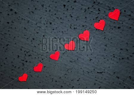 Small red hearts are arranged diagonally on a black background.