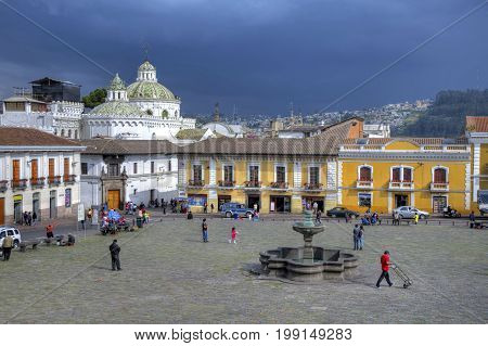 View of a church plaza in downtown Quito, with houses, rooftops, church domes and people. Quito, Pichincha, Ecuador.