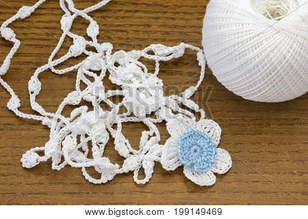 Handmade crochet white chain and a blue flower. Yarn ball for crochet or knitting on wooden table. Homemade necklace