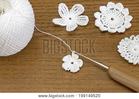 Wooden background with cotton crochet lace white flowers and crochet hook