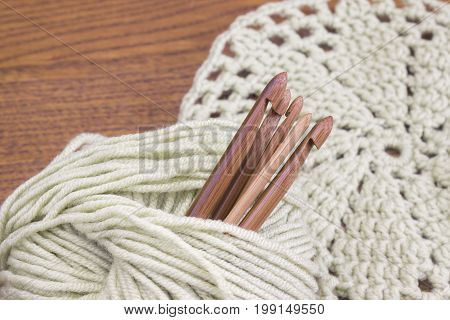 Wooden natural bamboo crochet hooks doily and yarn ball on the table. Creative work place for homemade crafts. Top view