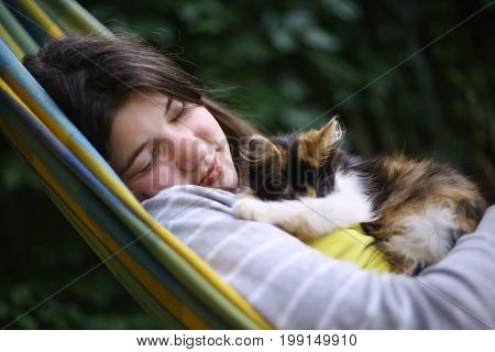 teenager girl nap in hammock with little kitten on summer garden background
