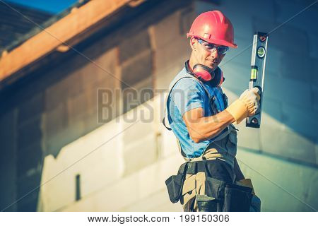 Construction Worker with Level Tool and the Construction Site.