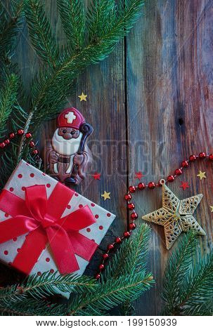 Saint Nicholas and gift on a wooden background with winter decor