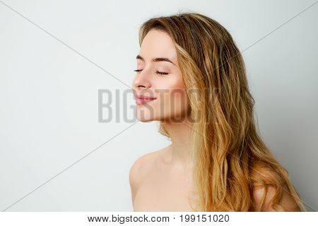 Beautiful Smiling Woman Profile Portrait. Happy Girl with Closed Eyes Fashion Portrait. Female with Long Hair. Pleasure Concept. Gray Background with Copy Space.